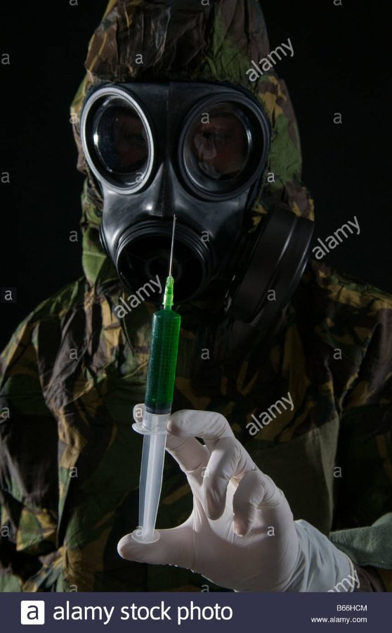 soldier-in-respirator-and-protective-suit-inspects-hypodermic-of-green-B66HCM.jpg