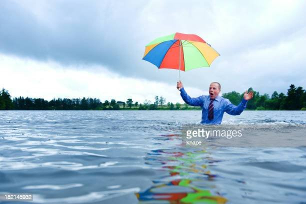 businessman-standing-waist-up-in-water-with-a-umbrella-picture-id182145932.jpeg.dd15773e7b3cc8d8c40a1ebc0f4bc1f3.jpeg